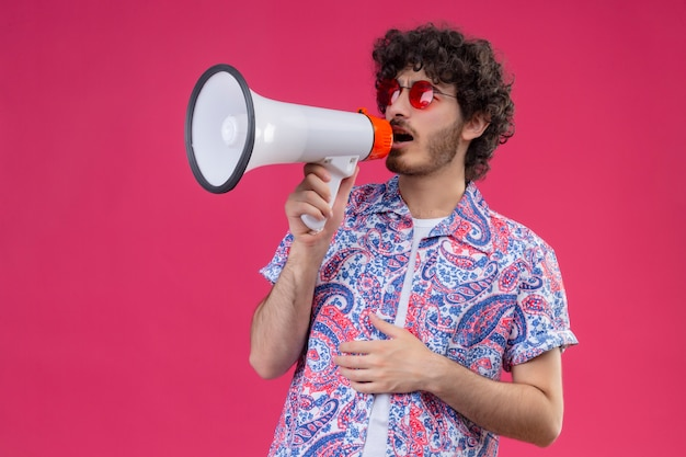 Junger hübscher lockiger mann, der sonnenbrillen trägt, die durch sprecher mit hand auf seinem bauch auf isolierter rosa wand mit kopienraum sprechen