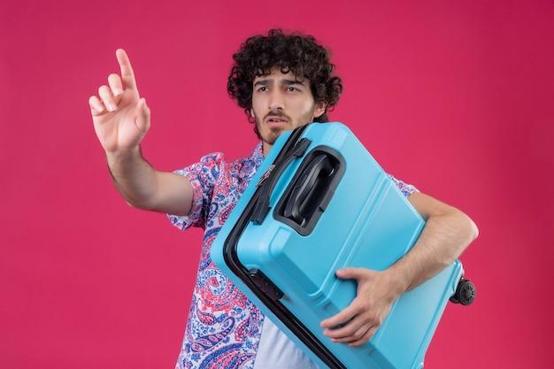 Junger hübscher lockiger reisender mann, der koffer hält und hand auf isolierter rosa wand ausdehnt