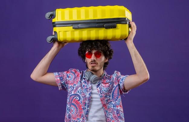 Junger hübscher lockiger reisender mann, der sonnenbrille und kopfhörer am hals hält, der koffer auf kopf auf isolierter lila wand hält