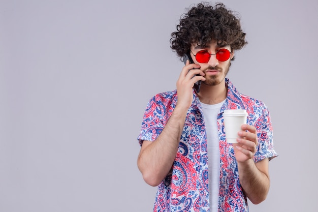 Junger hübscher lockiger reisender mann, der sonnenbrillen trägt, die am telefon sprechen und plastikkaffeetasse halten und es auf isolierter weißer wand mit kopienraum betrachten