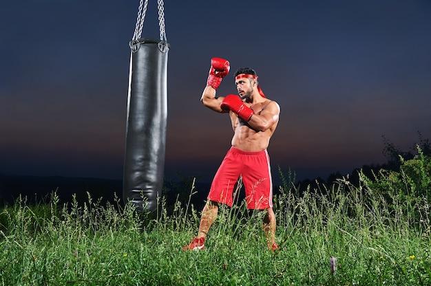 Junger hübscher männlicher boxer, der auf einem boxsack im freien übt