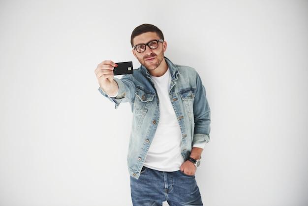 Junger hübscher männlicher geschäftsleiter in der freizeitkleidung, die eine kreditkarte in den taschen auf einem weißen hintergrund hält. das konzept des handels im internet und die leichtigkeit des elektronischen geldes.