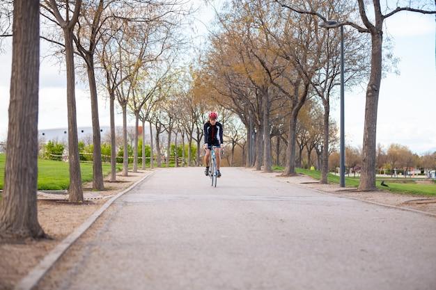 Junger hübscher männlicher radfahrer in der sportkleidung und im schutzhelm, die fahrrad auf straße im park radfahren