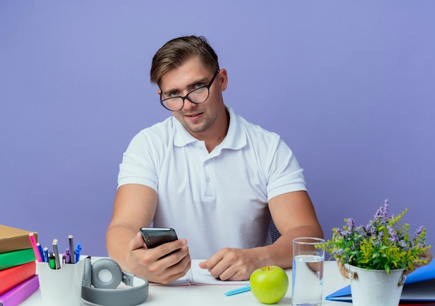 Junger hübscher männlicher student, der am schreibtisch mit schulwerkzeugen sitzt, die brille tragen und telefon lokalisiert auf blauer wand halten