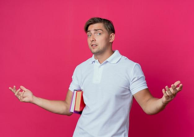 Junger hübscher männlicher student, der bücher hält und hände verbreitet, die auf rosa wand lokalisiert werden