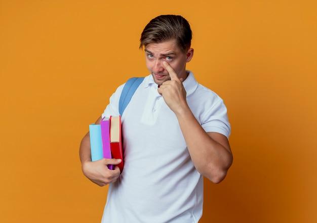 Junger hübscher männlicher student, der rückentasche trägt, die finger auf auge lokalisiert auf orange wand setzt