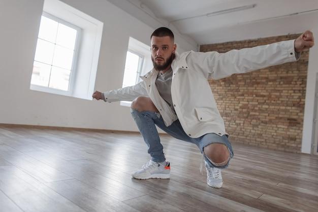 Junger hübscher männlicher tänzer in modekleidung mit zerrissenen jeans, die im studio aufwerfen