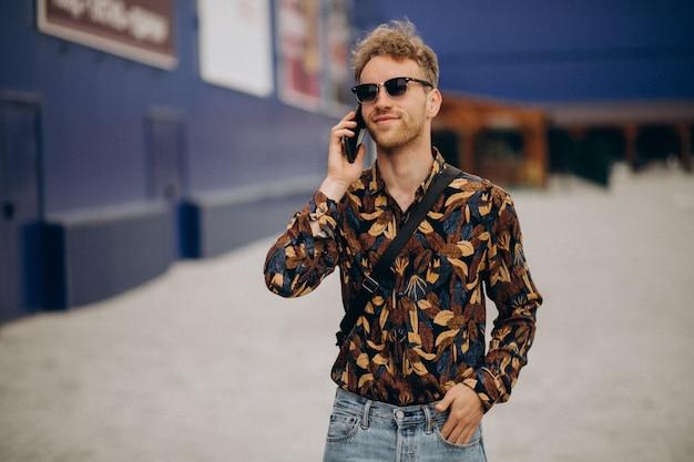 Junger hübscher mann, der am telefon spricht