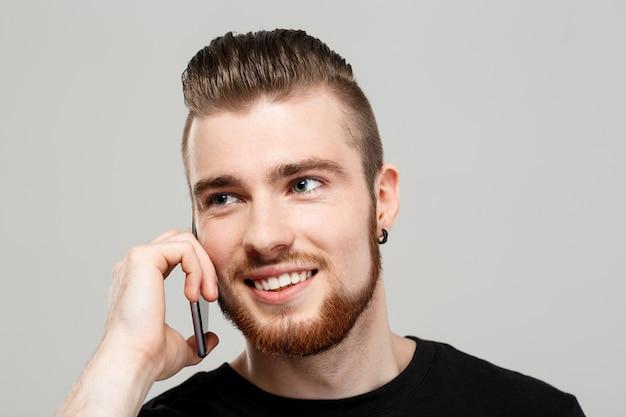 Junger hübscher mann, der am telefon über graue wand spricht.
