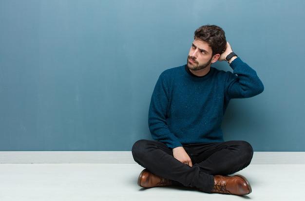 Junger hübscher mann, der auf boden sitzt und sich verwirrt und verwirrt fühlt, kopf kratzt und zur seite schaut