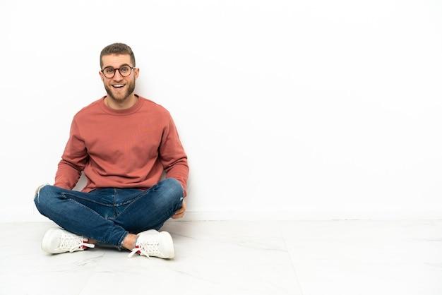 Junger hübscher mann, der auf dem boden mit überraschendem gesichtsausdruck sitzt