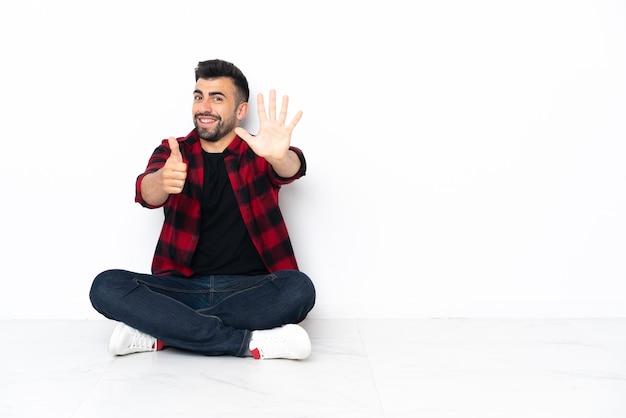 Junger hübscher mann, der auf dem boden sitzt und sechs mit den fingern zählt