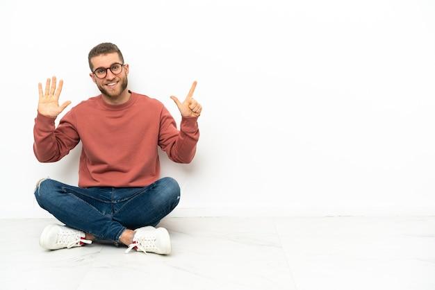 Junger hübscher mann, der auf dem boden sitzt und sieben mit den fingern zählt