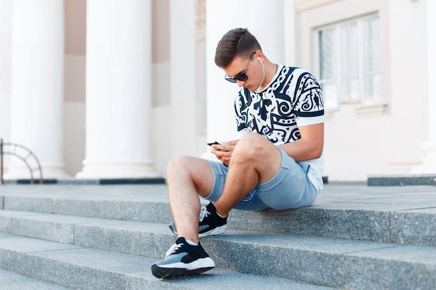 Junger hübscher mann, der auf den stufen sitzt und an ihrem telefon arbeitet.