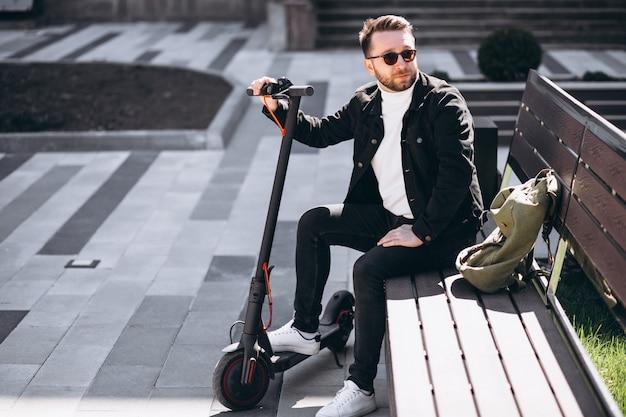 Junger hübscher mann, der auf der bank im park sitzt und sich von einer rollerfahrt ausruht