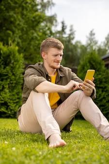Junger hübscher mann, der auf rasen im park ruht, der neue app auf handy überprüft, macht beitrag auf sozialen netzwerken, die spiele spielen. glücklicher hipster-typ schaut auf den bildschirm des mobiltelefons und genießt das lesen von nachrichten