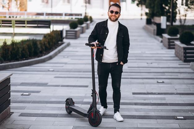 Junger hübscher mann, der auf roller im park reitet