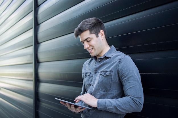 Junger hübscher mann, der auf seinem tablet-computer tippt