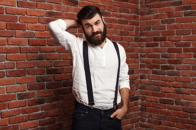 Junger hübscher mann, der auf ziegelmauer aufwirft.