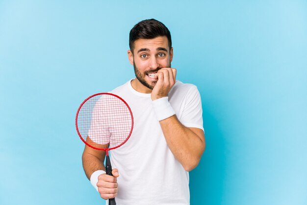 Junger hübscher mann, der badminton spielt