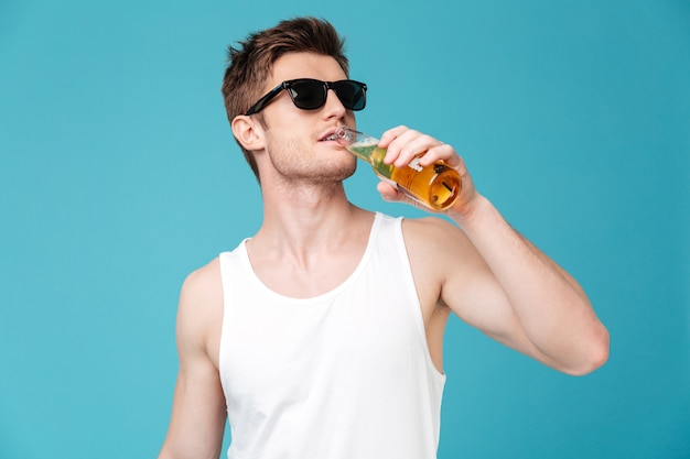 Junger hübscher mann, der bier trinkt