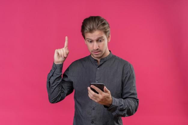 Junger hübscher mann, der bildschirm seines smartphones zeigt finger zeigt nach oben