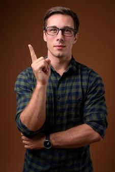 Junger hübscher mann, der brillen auf brauner wand trägt