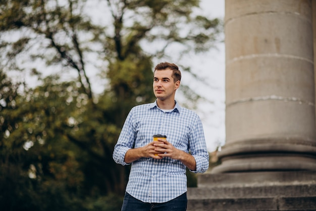 Junger hübscher mann, der draußen kaffee trinkt
