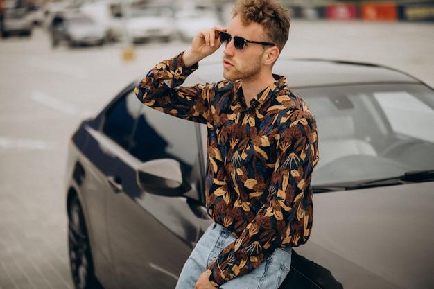 Junger hübscher mann, der durch auto steht
