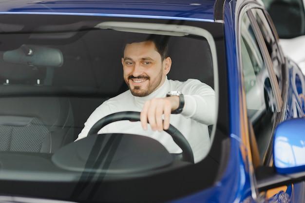 Junger hübscher mann, der ein auto in einem autoausstellungsraum wählt