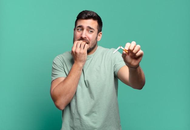 Junger hübscher mann, der eine zigarette hält. raucherentwöhnungskonzept