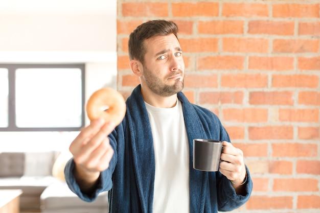 Junger hübscher mann, der einen kaffee zu hause trinkt