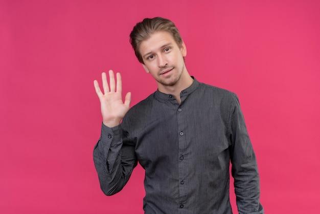 Junger hübscher mann, der freundliches winken mit der hand lächelt, die über rosa wand steht