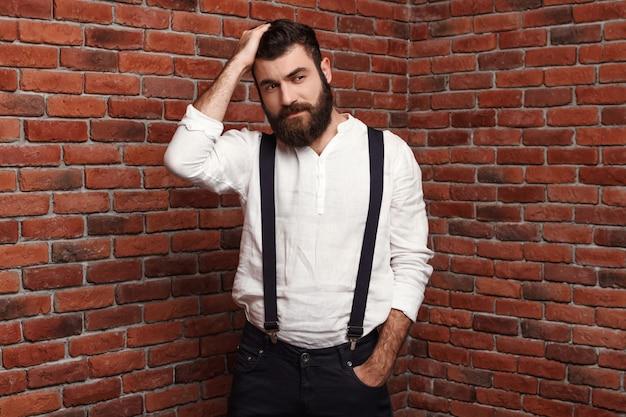 Junger hübscher mann, der frisur auf ziegelmauer korrigiert.