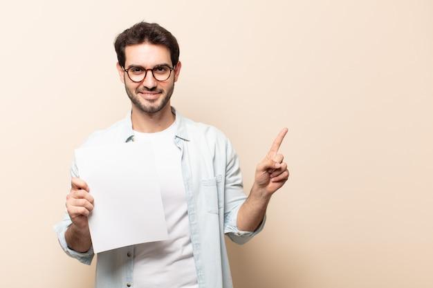 Junger hübscher mann, der fröhlich lächelt, sich glücklich fühlt und zur seite und nach oben zeigt, objekt im kopienraum zeigt