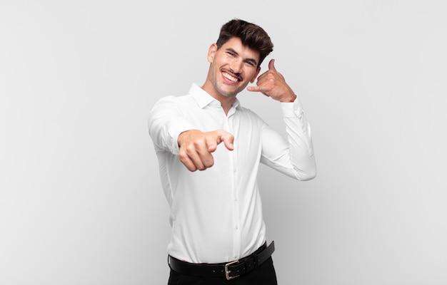 Junger hübscher mann, der fröhlich lächelt und nach vorne zeigt, während sie einen anruf tätigen, den sie später gestikulieren und am telefon sprechen