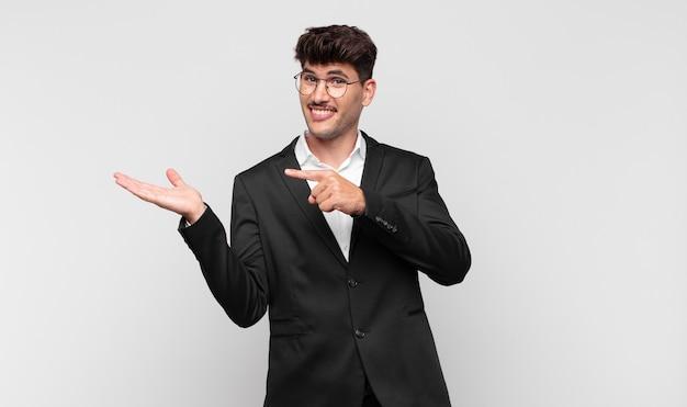 Junger hübscher mann, der fröhlich lächelt und zeigt, um raum auf handfläche auf der seite zu kopieren, ein objekt zeigend oder werbend