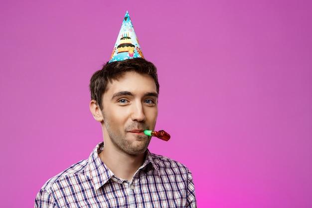 Junger hübscher mann, der geburtstagsfeier über lila wand feiert.