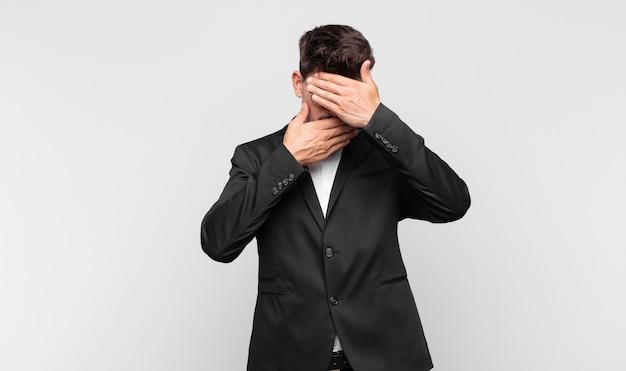 Junger hübscher mann, der gesicht mit beiden händen bedeckt, sagt nein zur kamera! bilder ablehnen oder fotos verbieten