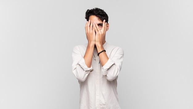 Junger hübscher mann, der gesicht mit händen bedeckt, mit überraschtem ausdruck zwischen den fingern späht und zur seite schaut