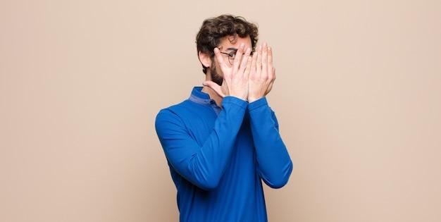 Junger hübscher mann, der gesicht mit händen bedeckt, zwischen fingern mit überraschtem ausdruck späht und zur seite gegen flache wand schaut