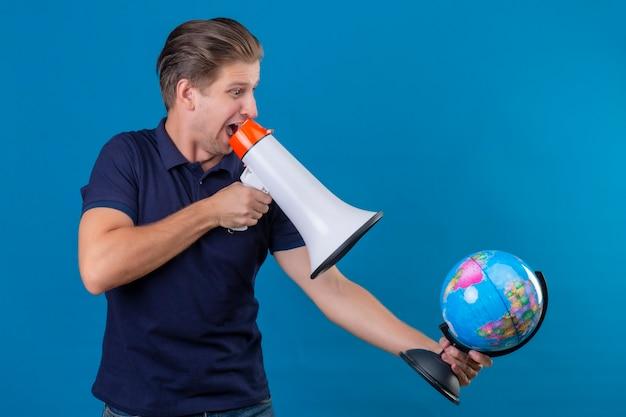 Junger hübscher mann, der globus hält, der zu megaphon spricht, überrascht und verlassen steht über blauem hintergrund