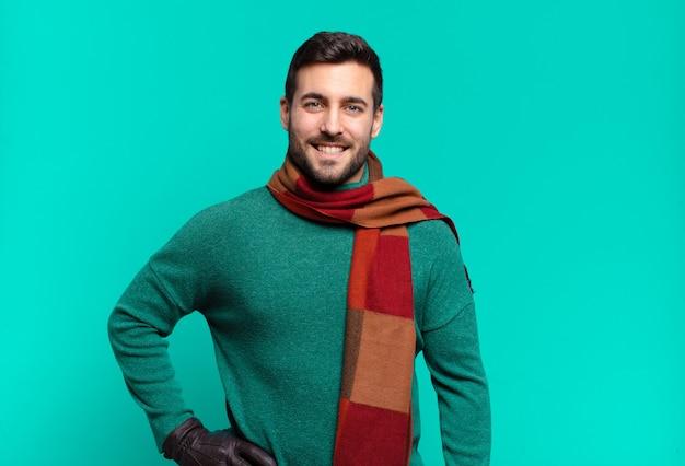 Junger hübscher mann, der glücklich mit einer hand auf hüfte und selbstbewusster, positiver, stolzer und freundlicher haltung lächelt
