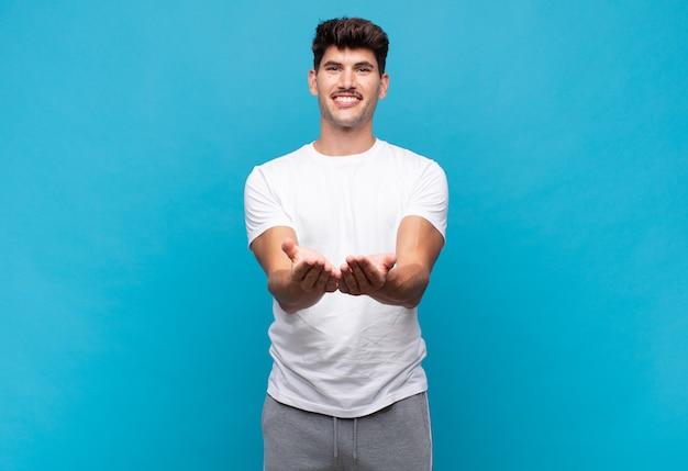 Junger hübscher mann, der glücklich mit freundlichem, selbstbewusstem, positivem blick lächelt und ein objekt oder konzept anbietet und zeigt