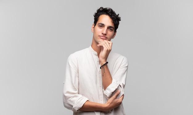 Junger hübscher mann, der glücklich schaut und mit der hand am kinn lächelt, sich wundert oder eine frage stellt, optionen vergleicht
