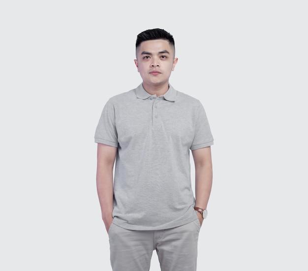 Junger hübscher mann, der graues poloshirt trägt