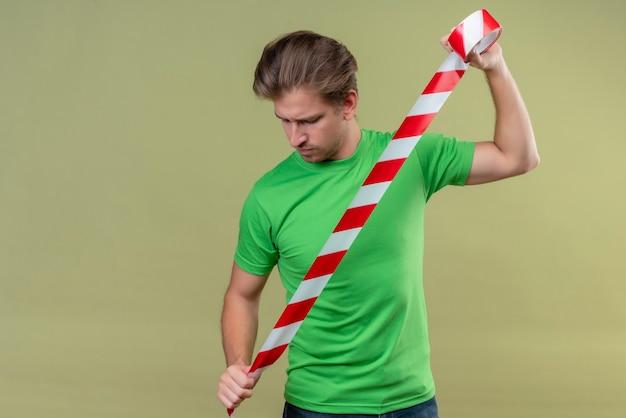 Junger hübscher mann, der grünes t-shirt hält, das klebeband hält und verwendet, das mit ernstem ausdruck auf gesicht steht, das über grüner wand steht