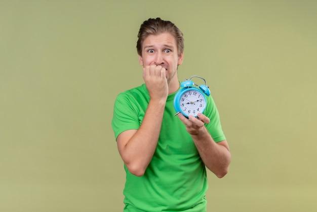 Junger hübscher mann, der grünes t-shirt hält, das wecker hält, der gestresste und nervöse beißende nägel steht, die über grüner wand stehen