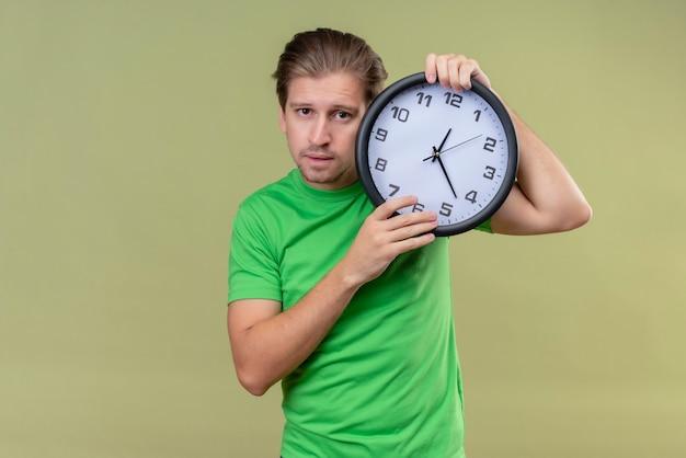 Junger hübscher mann, der grünes t-shirt hält uhr mit traurigem ausdruck auf gesicht steht, das über grüner wand steht