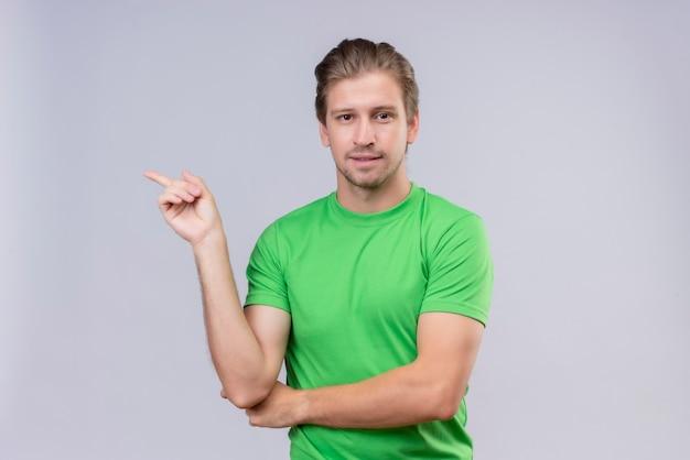 Junger hübscher mann, der grünes t-shirt lächelnd und mit zeigefinger zur seite zeigend trägt